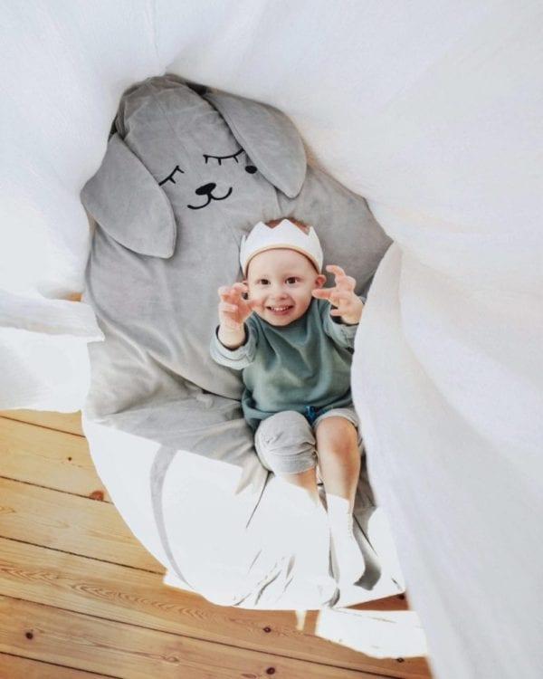 Chłopiec w koronie siedzi na puf szary zając