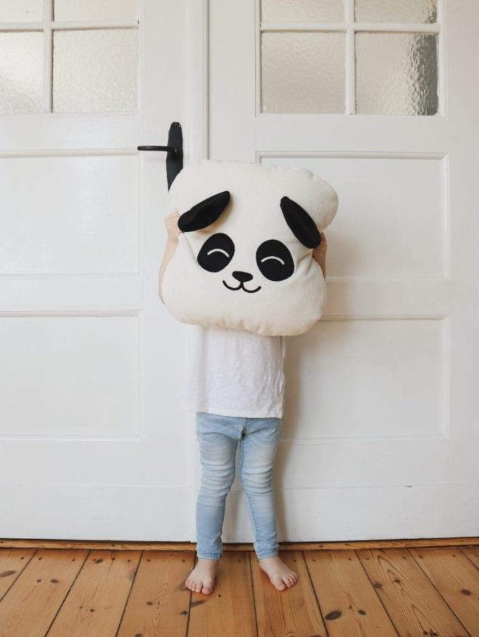 Poduszka biała panda chłopiec trzymający na wysokości głowy