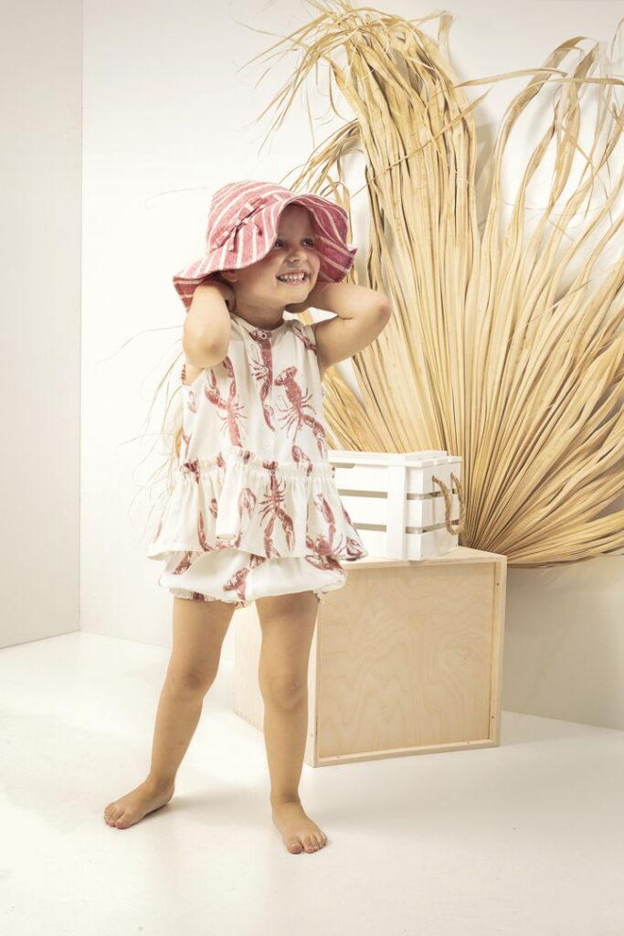 dziewczynka w bloomerdsch bluzeczce lobster pink i kapelusz z rondem len rozowe paski